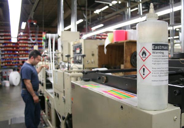 GHS-labeled-bottle-on-press